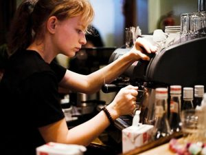 Young woman student employed as a barista for a sumemr job