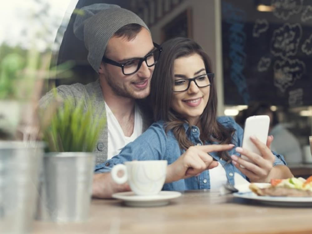 Smiling young couple look up the six Cs of success for cash and couples on her phone