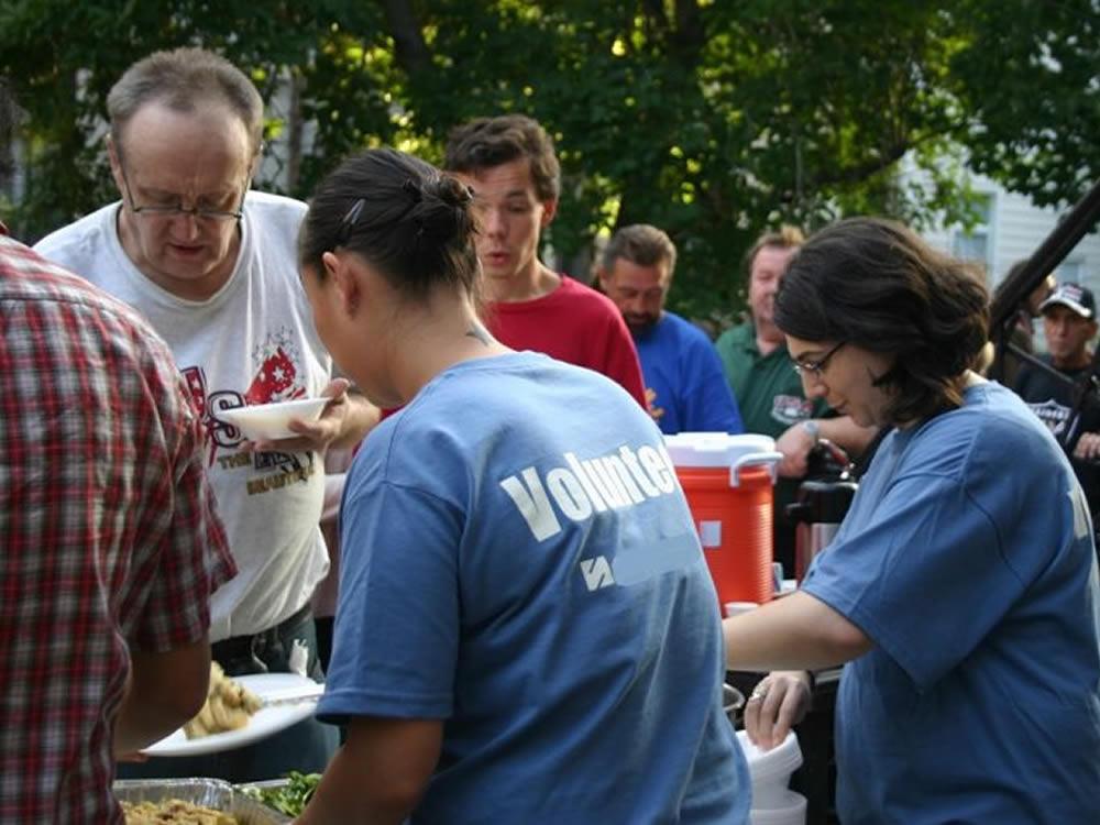 Volunteer line serving meals, giving sagely of their time and effort