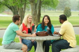 Four teens at outdoor table brainstorm questions for college visits