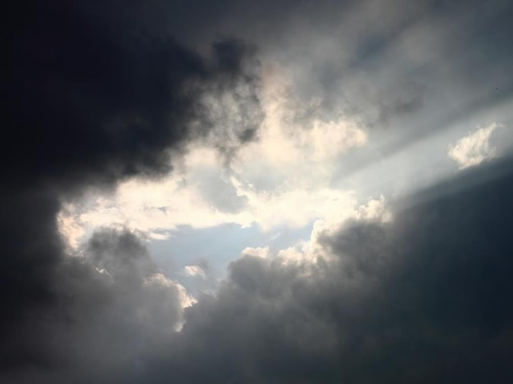 Sunbeams through clouds, symbolizing death of a family member