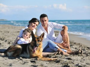 Family and dog on beach near where they want to buy a vacation home