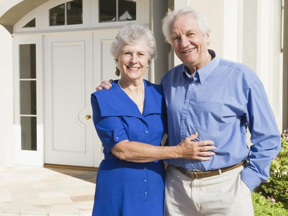 Smiling older couple in front of house they financed with reverse mortgages in retirement