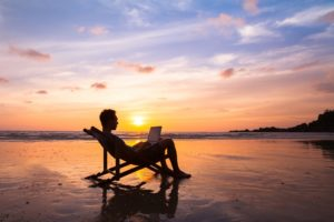 Man sitting on beach with laptop has mastered the art of knowing how to simplify your finances
