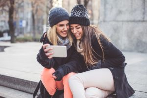 Two young women on bench looking at best financial apps for teens and young adults on iPhone