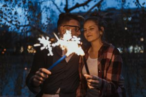 Couple with sparklers look forward to a wealthy New Year with 2019 financial New Year resolutions