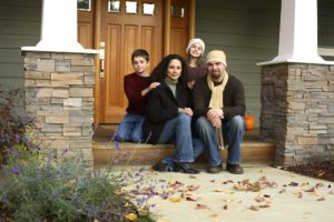 Blended family on porch of their new home in fall consider financial planning for blended families