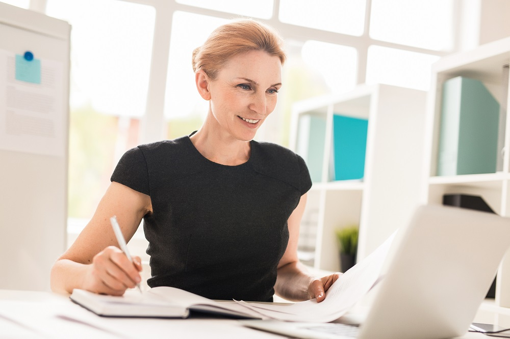 Woman tax planner at desk considers new rules for Roth IRA conversions