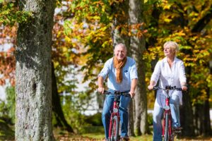Couple biking in park enjoy freedom at age 70 with maximum Social Security Benefits and RMDs