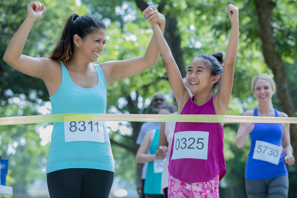 Mother and daughter completing race together symbolizes the drive and competitiveness involved in parental peer pressure