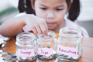 Little girl understands that saving and spending milestones for kids help with financial learning