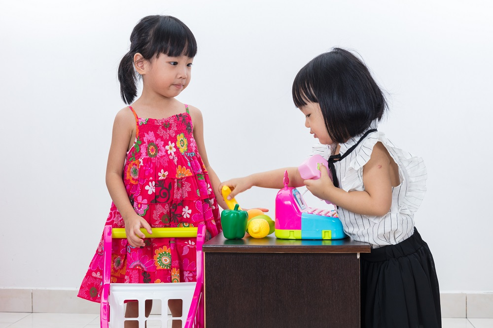 Fun money activities for kids includes playing shop, like these two little girls