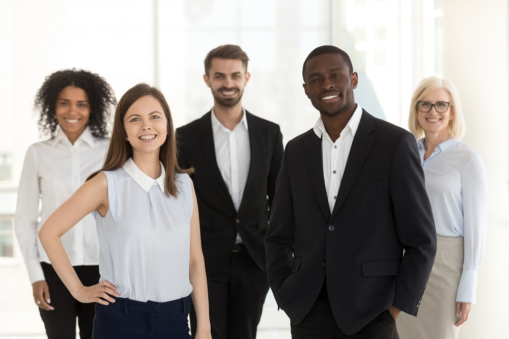 Happy group of five diverse employees, considering their Roth IRA and Roth 401(k) options for retirement saving