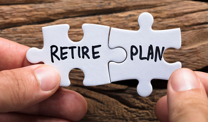Hands holding jigsaw pieces showing retire and plan reflect the important of financial planning for retirement